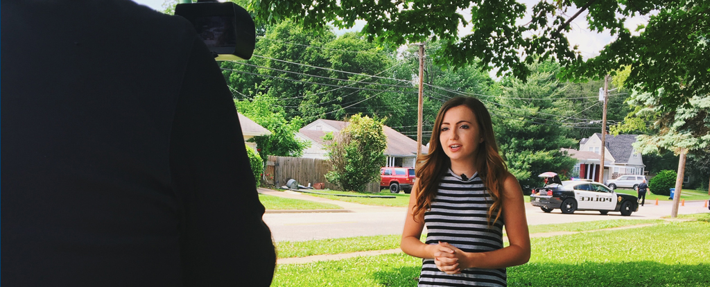 Rachel Haik speaking in front of a camera, on the job at her local news reporting internship